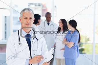 Mature doctor pointing at something on his clipboard