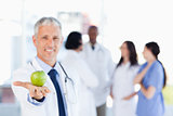 Mature doctor holding a green apple