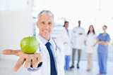 Green apple held by a doctor with a team behind him