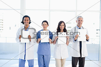 Four medical people standing upright while holding blank sheets