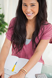 Portrait of a smiling brunette student using a laptop