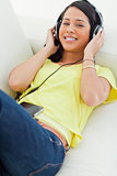 High-angle view of a young Latino listening music on a smartphon