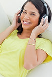 Portrait of a smiling Latino listening music on a smartphone