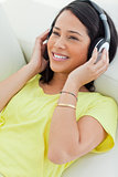 Close-up of a smiling Latino listening music on a smartphone