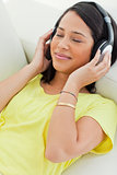 Close-up of a smiling Latino enjoying music on a smartphone