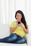 Portrait of a happy Latino looking her smartphone