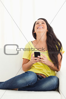 Happy Latino looking up while holding her smartphone