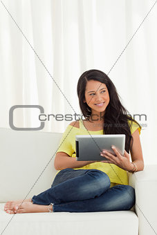 Beautiful Latino smiling while using a touch pad