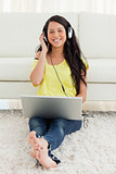 Portrait of a smiling Latin listening to music on a laptop