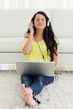 Pretty Latin enjoying music on a laptop