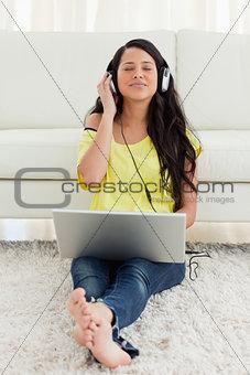 Pretty Latin enjoying music on a laptop