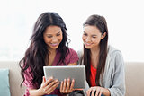 A woman with her friend smiling as they both look at the tablet 