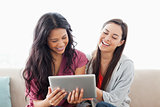 A laughing pair of women on the couch watching their tablet pc 