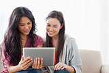 A woman holding a tablet with her friend on the couch as they wa
