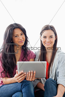 Close up of two women sitting on the couch while looking at the