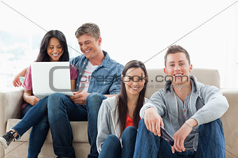 A man and woman sitting on the ground while another man and woma