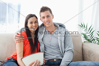 A smiling couple sitting on the couch look into the camera