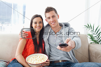 A couple embracing while on the couch changing the channel