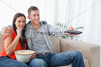Side view shot of a couple smiling as they change the tv channel