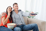 An embracing laughing couple enjoying a tv show as they eat popc