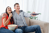A laughing couple enjoying a tv show together as they hold each