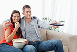 A couple eating popcorn and using the tv remote while looking at