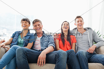 A group of laughing friends look into the camera