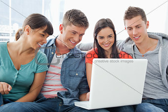 A smiling group of friends sitting around a laptop