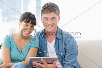 A smiling couple hold a tablet pc while looking at the camera