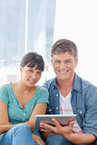 Close up of a smiling couple with a tablet pc looking into the c