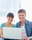 A smiling couple with a laptop as they look into the camera