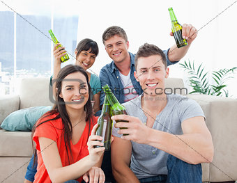A celebrating group of friends with beers in hand