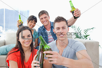 A group of friends celebrating by clinking bottles together