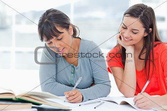 One girl looks over into the work of her friend