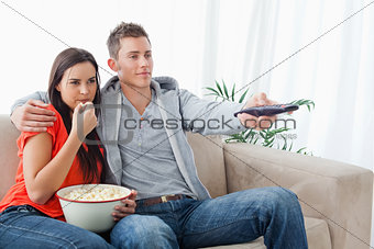 A couple sitting together embracing as they watch tv and eat pop