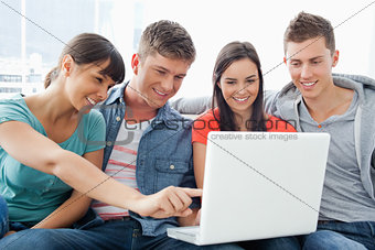 A smiling group of friends looking at the laptop with one girl p