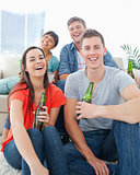 A laughing group sitting on the couch and the floor with beers i