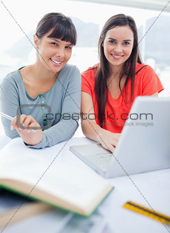 Close up shot of a girl and her friend smiling as they sit with