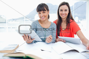 A pair of smiling girls doing work with tablets as they look int