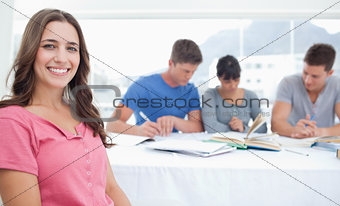 A smiling woman sits in front of her three friends who are study