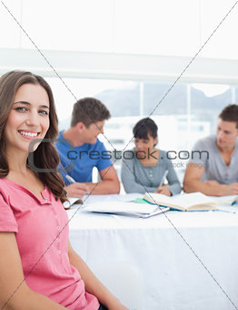 A side view of a woman sitting in front of her friends as she lo