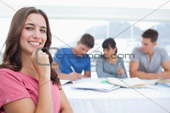 A woman smiling with a hand on her chin as her friends sit in th