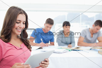 A smiling woman in front of her friends on her tablet