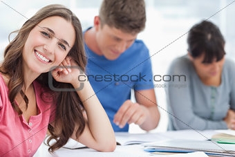 A smiling woman rests her head on her hand as she looks at the c