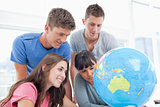 Four students look at the globe together