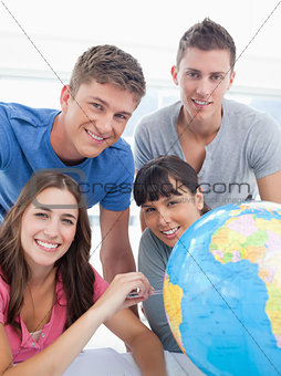A group of friends beside a globe looking into the camera