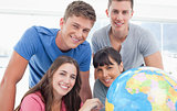 A smiling group of people looking into the camera with a globe b