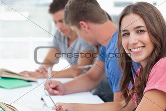A smiling woman looking at the camera as her friends sit in the