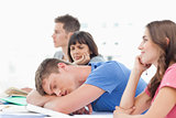 A sleeping student is being looked at by a confused fellow stude
