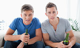 Two guys looking into the camera with beer in hand